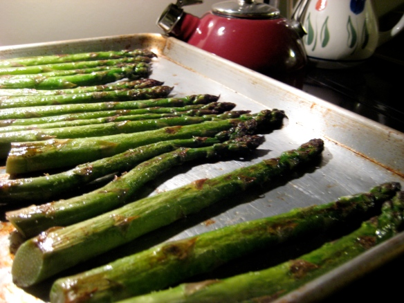 Roasted asparagus spears line a baking sheet, fresh from the oven.