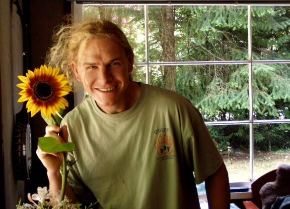 Andy with organic sunflower grown on Gabriola Island, BC, July 2003.