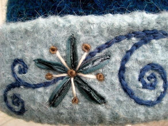 French knots, split-stitch and lazy daisy stitches all contribute to the embroidery design.