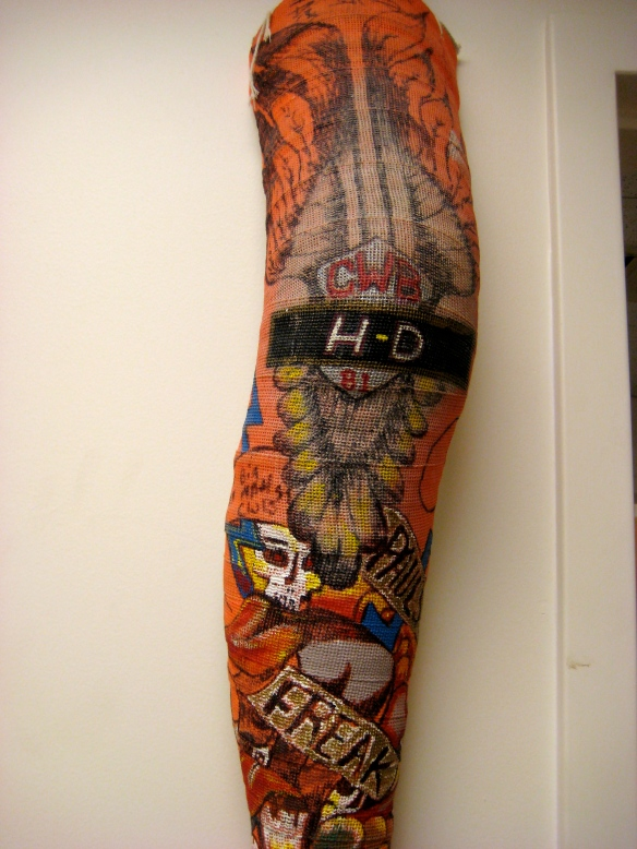 "Intricate Harley-Davidson artwork ""tattoo"" on an orange fiberglass full-leg cast."
