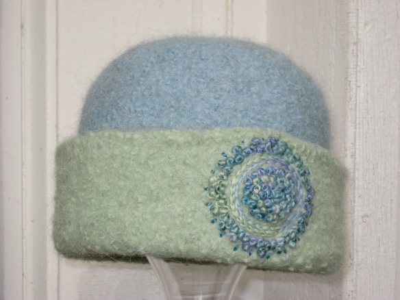 Freehand embroidery of French knots on icy sea foam felt hat by fiber artist, Carrie Cahill Mulligan of Canaan, New Hampshire.