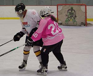 Retired kindergarten teacher, Ceci takes onretired fireman, Dave for the puck at Learn-to-Play Hockey at Campion Rink.