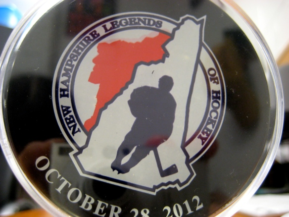 Hockey puck commemorating Coach Dick Dodds' recognition as a New Hampshire Legend of Hockey on October 28, 2012.