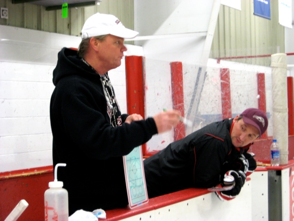 Coach Dodds explains an on-ice hockey drill for the adult Learn-to-Play group.