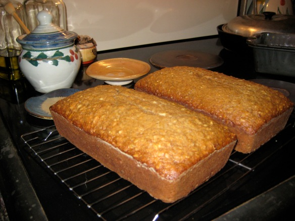 Fresh loaves of banana nut bread cooling on a rack.