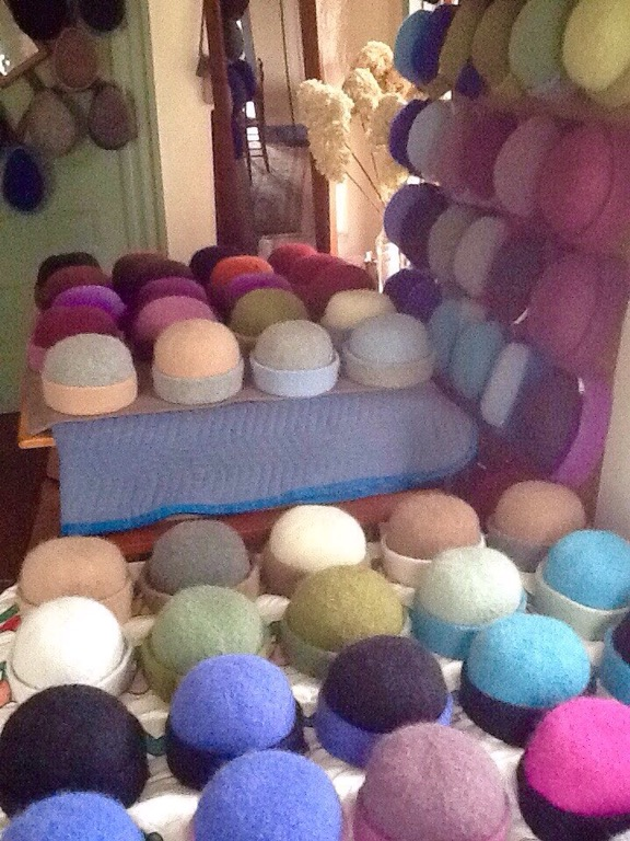 Recently felted & hand-shaped, felt hats in every color dry in the home studio of NH fiber artist, Carrie Cahill Mulligan.